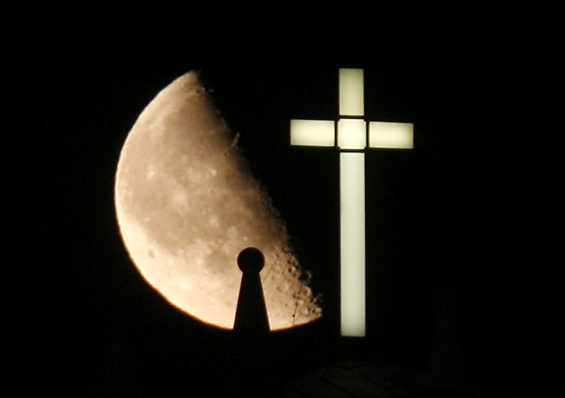 A third quarter Buck Moon rises behind a spire on the top of the bell tower next to a lighted cross