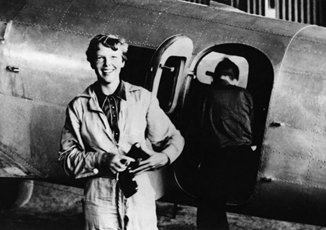 Amelia Earhart standing by her Lockheed Electra with Fred Noonan in the background