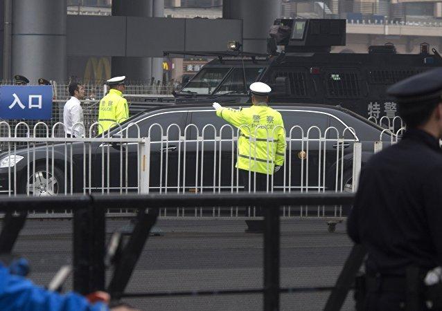 Une limousine sans numéros d'immatriculation arrive à la gare de Pékin sous un gros dispositif de sécurité