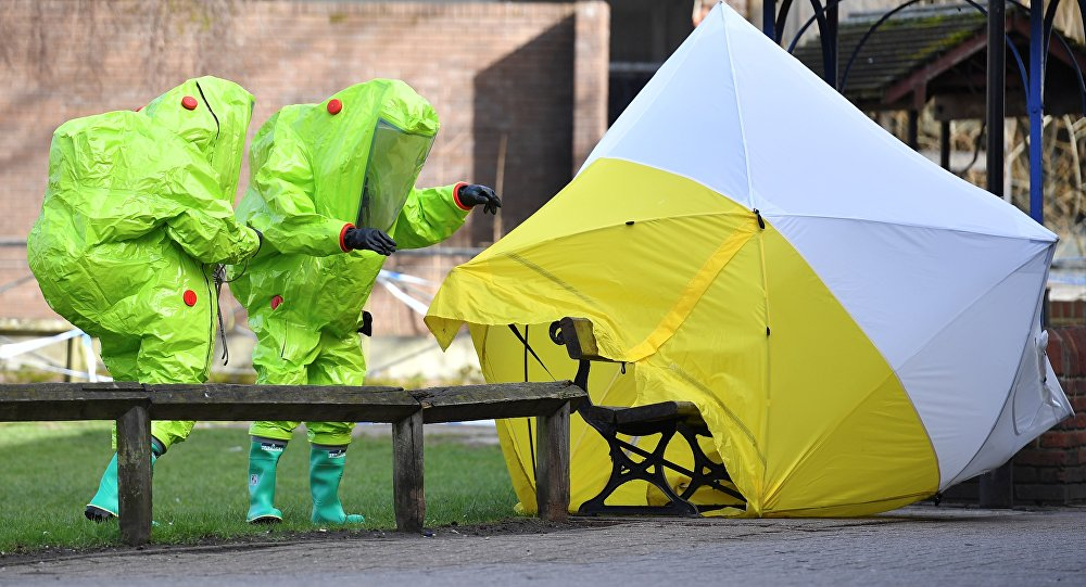 In this file photo taken on March 8, 2018 members of the emergency services in green biohazard encapsulated suits re-affix the tent over the bench where Russian spy Sergei Skripal and his daughter Yulia were found in critical condition on March 4 at The Maltings shopping centre in Salisbury, southern England