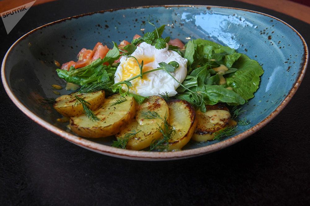 Salade au saumon, œuf poché et pommes de terre au restaurant à burgers Bureau