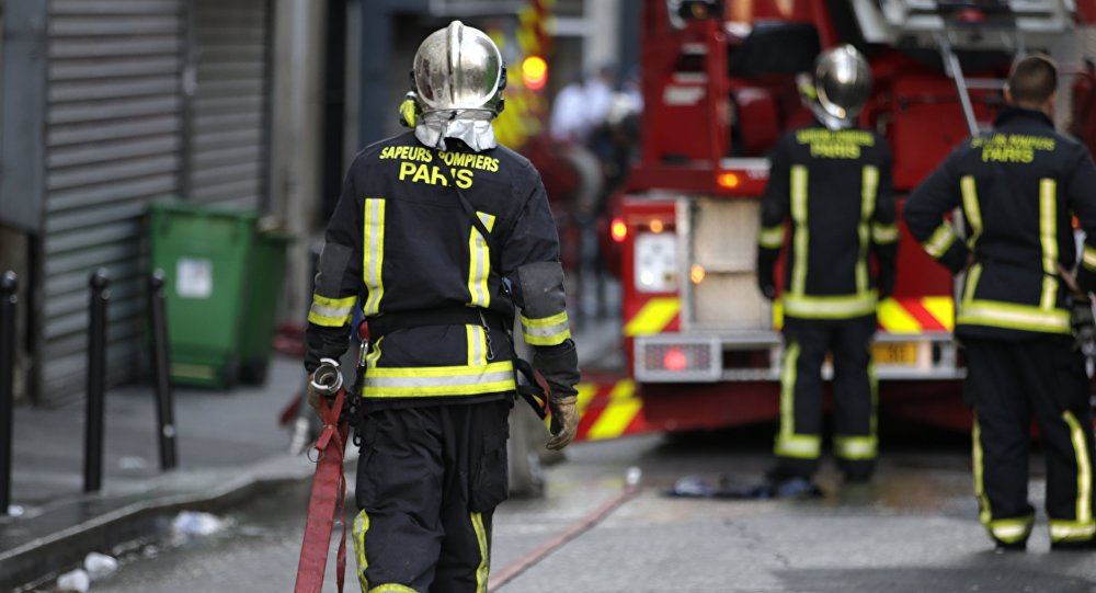 Firefighters work at the scene where a fire in an apartment building in the Myrha street, north of Paris, killed eight people early on September 2, 2015.