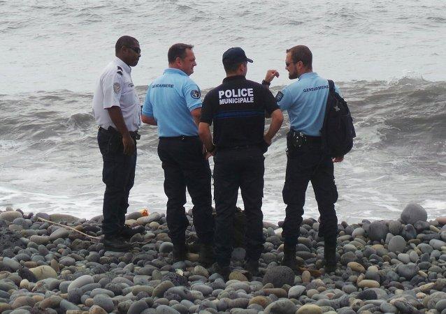 Des policiers et gendarmes français sur la plage de La Réunion où un débris d'avion a été retrouvé en 2015
