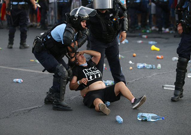 Police stand near protester during a demonstration in Bucharest