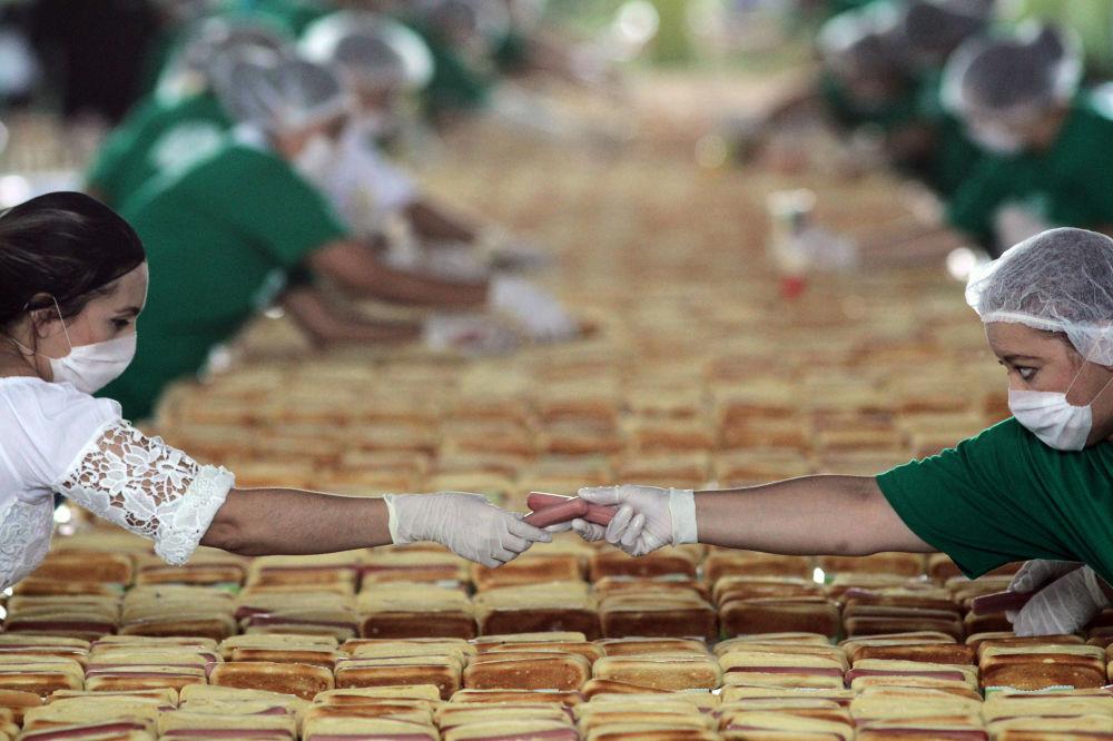 Des Mexicains préparent des hot-dogs pour battre le record Guinness de la plus longue file de hot-dogs à Guadalupe, au Mexique