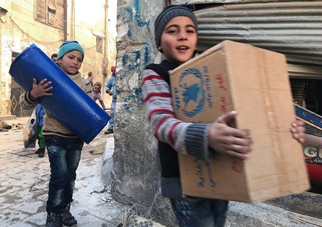 Des enfants reçoivent de l'aide humanitaire à Alep