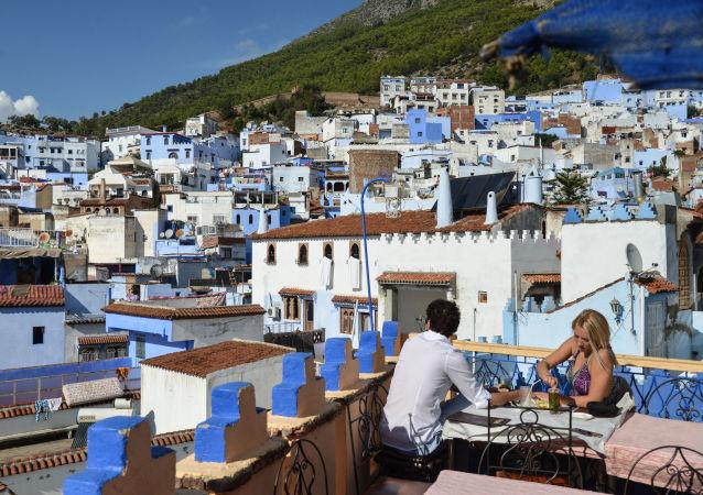 Les clients d'un café sur le toit d'un immeuble à Chefchaouen, Maroc
