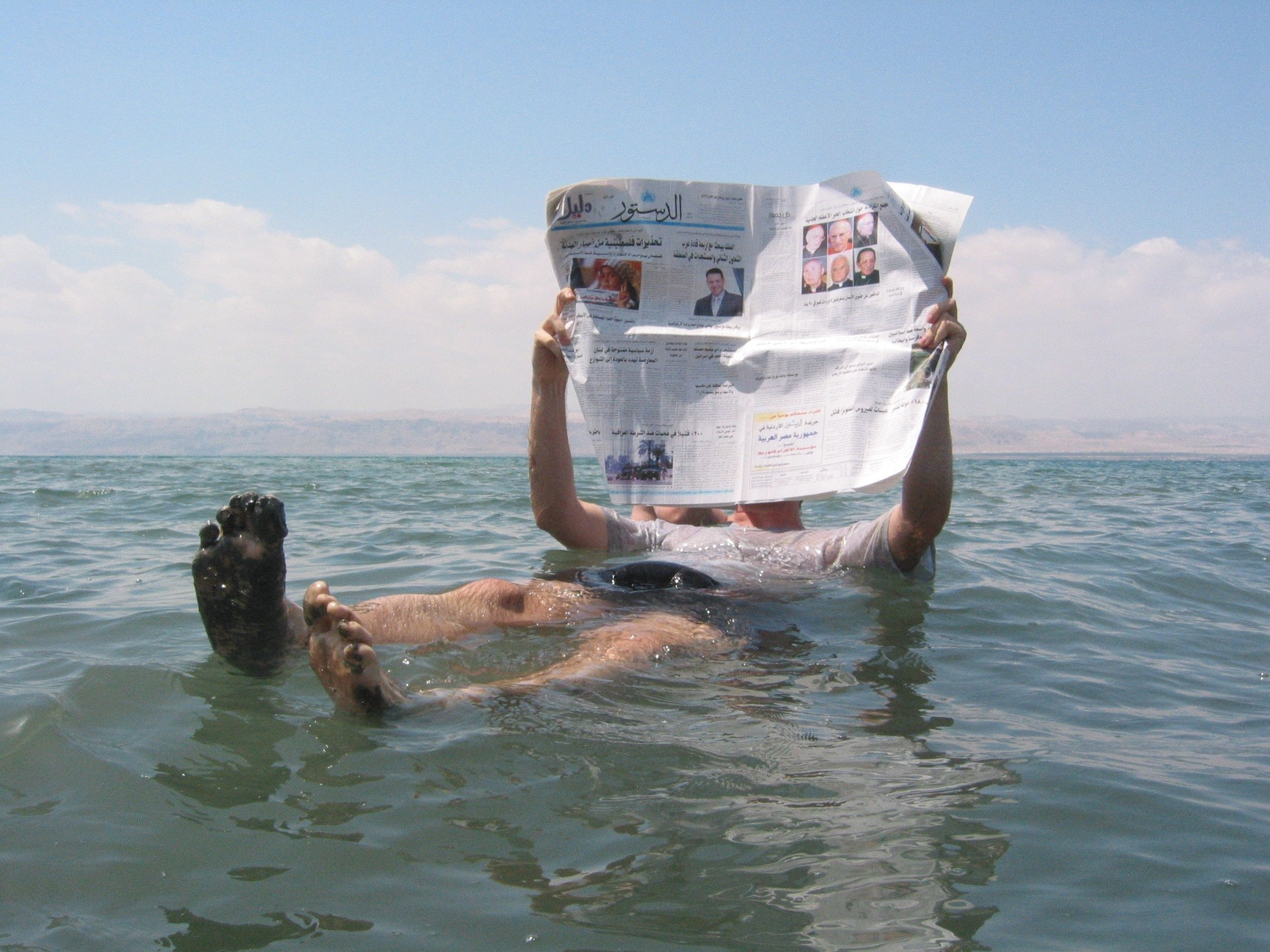 Un homme lit un journal en mer Morte