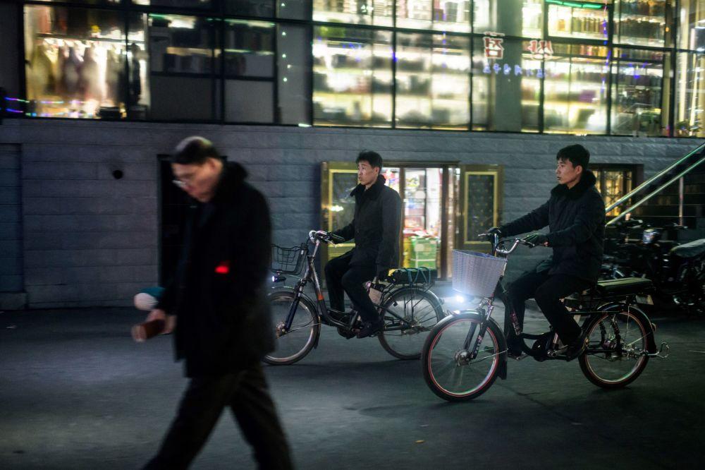 Des passants dans la rue de la ville frontalière de Sunuiju en Corée du Nord.
