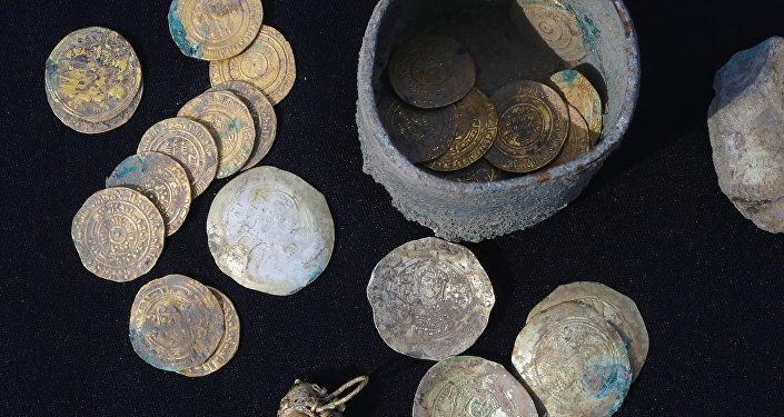 Un pot contenant 24 pièces d'or et des boucles d'oreille du même métal retrouvé lors de fouilles dans un quartier ancien de la ville israélienne de Césarée
