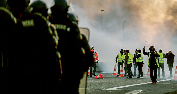Des individus se tiennent face aux gendarmes sur une route de Caen le 18 novembre 2018.