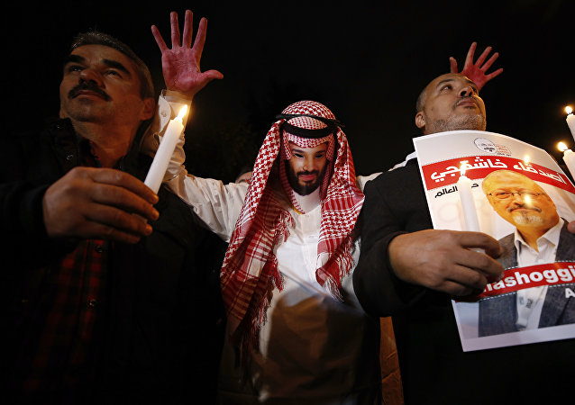 An activist, wearing a mask depicting Saudi Crown Prince Mohammed bin Salman, holds up his hands, painted with fake blood as he protests the killing of Saudi journalist Jamal Khashoggi, during a candlelight vigil outside Saudi Arabia's consulate in Istanbul, Thursday, Oct. 25, 2018