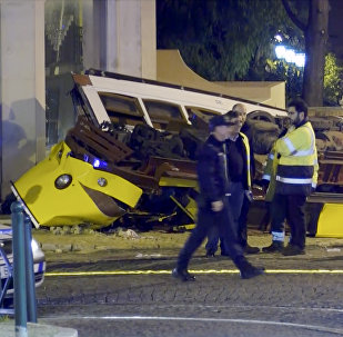 In this image taken from video, emergency service personnel work at the scene of a tram accident, Friday, Dec. 14, 2018, in Lisbon, Portugal.