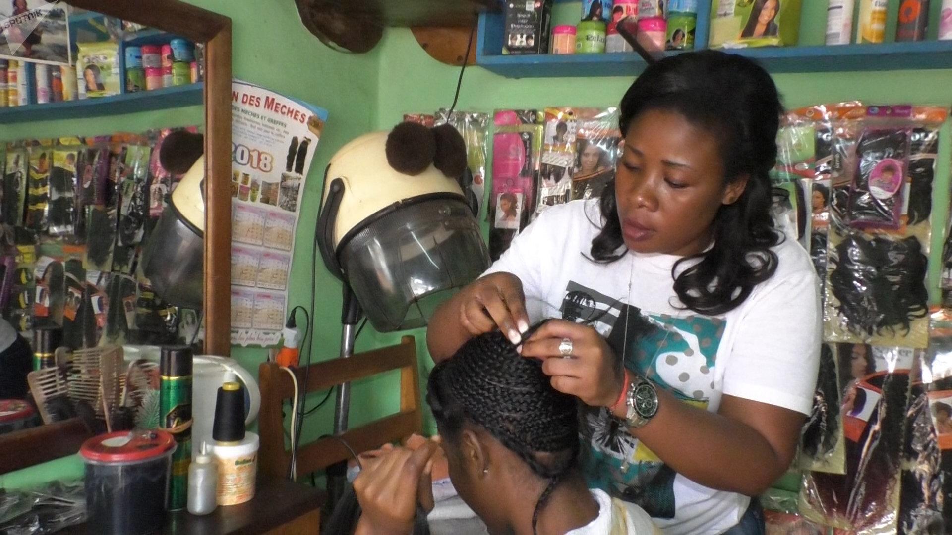 Anastasie, coiffeuse, en pleine séance de pose d'extensions naturelles. Cameroun
