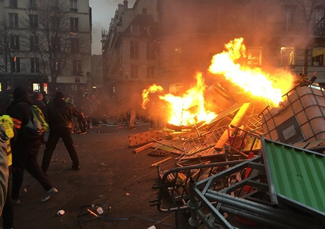 Gilets jaunes à Paris: de nombreux véhicules, des rebords de route en flammes