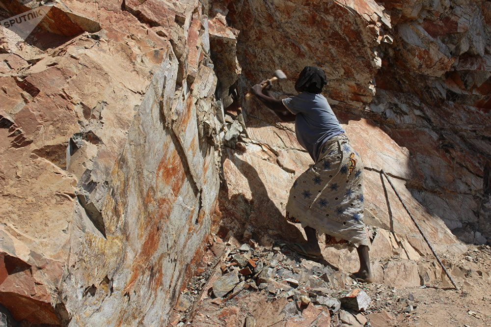 Adjawa arrache de gros morceaux de pierre au flanc de la montagne, Cameroun