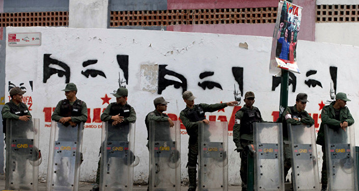 National Guard soldiers stand guard outside a polling station where a wall is covered with stencil paintings depicting the eyes of Venezuela's late President Hugo Chavez, during congressional elections in Caracas, Venezuela, Sunday, Dec. 6, 2015