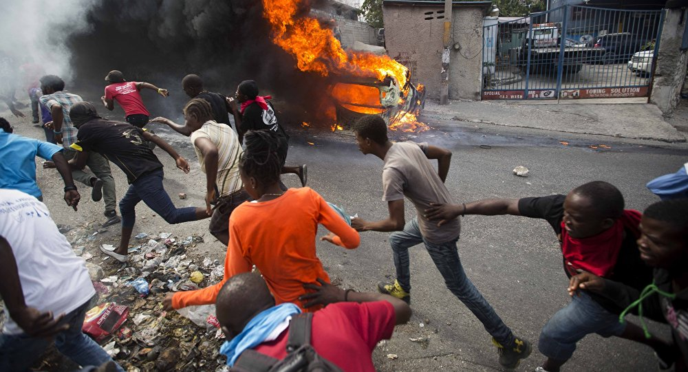 Demonstrators run away from police who are shooting in their direction, as a car burns during a protest demanding the resignation of Haitian President Jovenel Moise in Port-au-Prince, Haiti, Tuesday, Feb. 12, 2019.