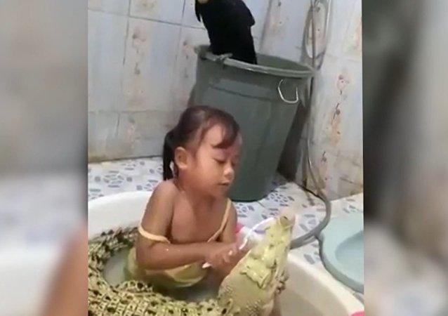 Cette petite fille brosse les dents d'un crocodile comme elle brosserait les siennes