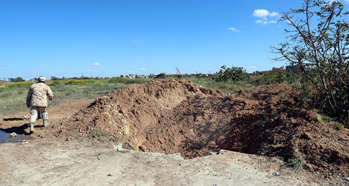 A crater is seen at the blast site after an air strike at Mitiga airport in Tripoli