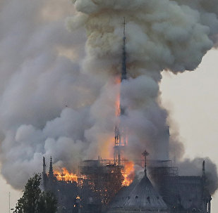 Flames and smoke are seen billowing from the roof at Notre-Dame Cathedral in Paris on April 15, 2019. A fire broke out at the landmark Notre-Dame Cathedral in central Paris, potentially involving renovation works being carried out at the site, the fire service said.