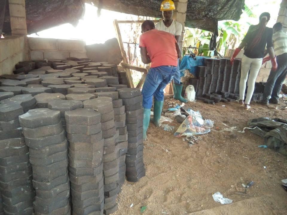 Des jeunes de la fondation Cœur d'Afrique à l'œuvre dans l'un des ateliers de fabrication de pavés écologiques.