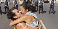 Пара целуется напротив заслона полиции во время забастовки Национального союза студентов в Бразилии