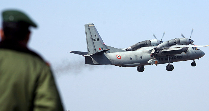 A soldier stands guard as an Indian Air Force AN-32 transport aircraft.