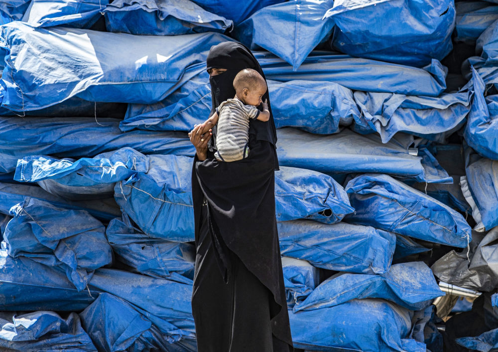 A woman wearing a niqab (full face veil) walks carrying an infant at al-Hol camp for displaced people in al-Hasakeh governorate in northeastern Syria on July 22, 2019, as people collect UN-provided humanitarian aid packages.