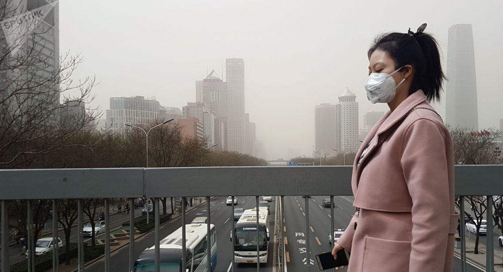 Жительница Пекина в защитной маске во время смога.