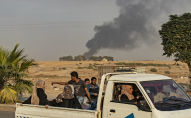 Civilians ride a pickup truck as smoke billows following Turkish bombardment on Syria's northeastern town of Ras al-Ain in the Hasakeh province along the Turkish border on October 9, 2019