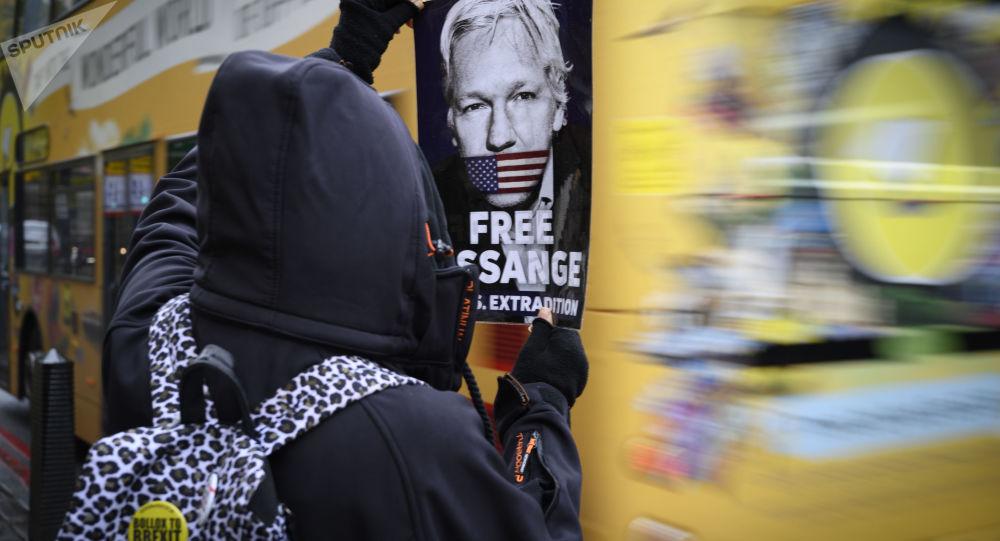 Un manifestant avec une affiche réclamant la libération de Julian Assange