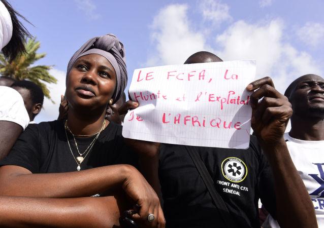 Un homme brandit une pancarte contre le franc CFA