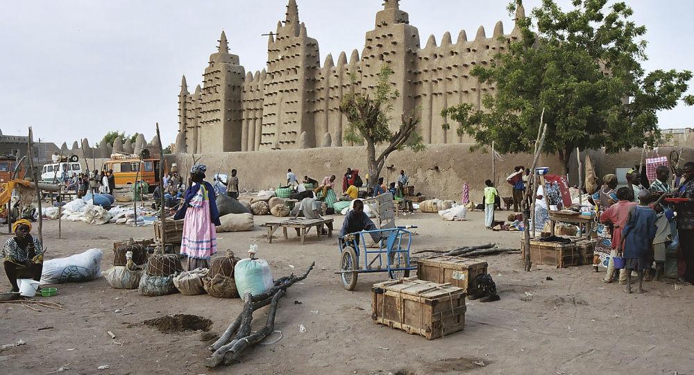 Un marché et la Grande Mosquée de Djenné, ville située dans la région malienne de Mopti.