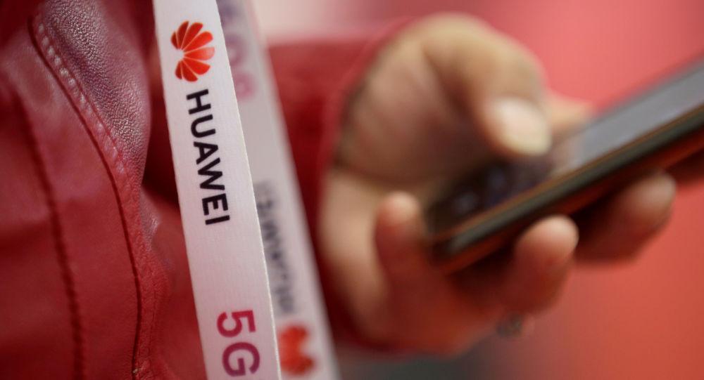 Un participant porte une bande de badge avec le logo de Huawei et un signe pour la 5G à l'exposition mondiale 5G à Pékin, Chine le 22 novembre 2019