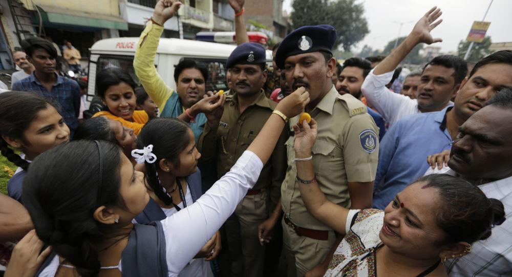 Des Indiennes offrent des gâteaux aux policiers et scandent des slogans en leur honneur pour célébrer le meurtre des quatre hommes soupçonnés d'avoir violé et tué une femme à Shadnagar.