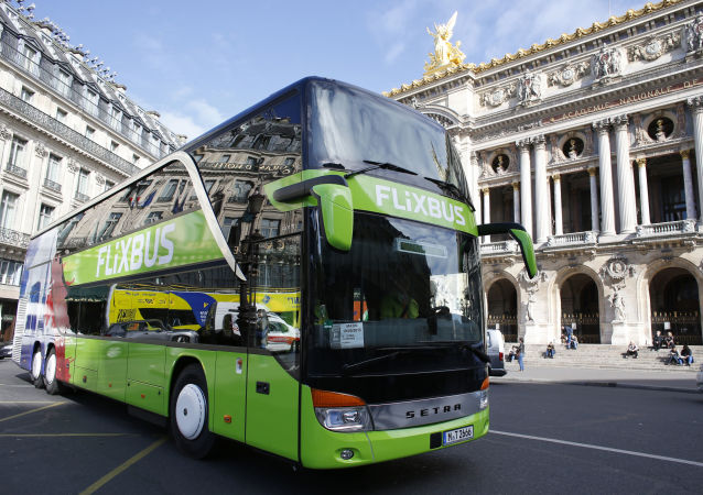 A bus of the German intercity bus service FlixBus drives past the Palais Garnier opera house on May 19, 2015 in Paris. The leader in transport services by bus in Germany, the start-up Flixbus, launched its services in Paris on May 19, 2015. The company now operates in 15 European countries. AFP PHOTO / THOMAS SAMON (Photo by THOMAS SAMSON / AFP)
