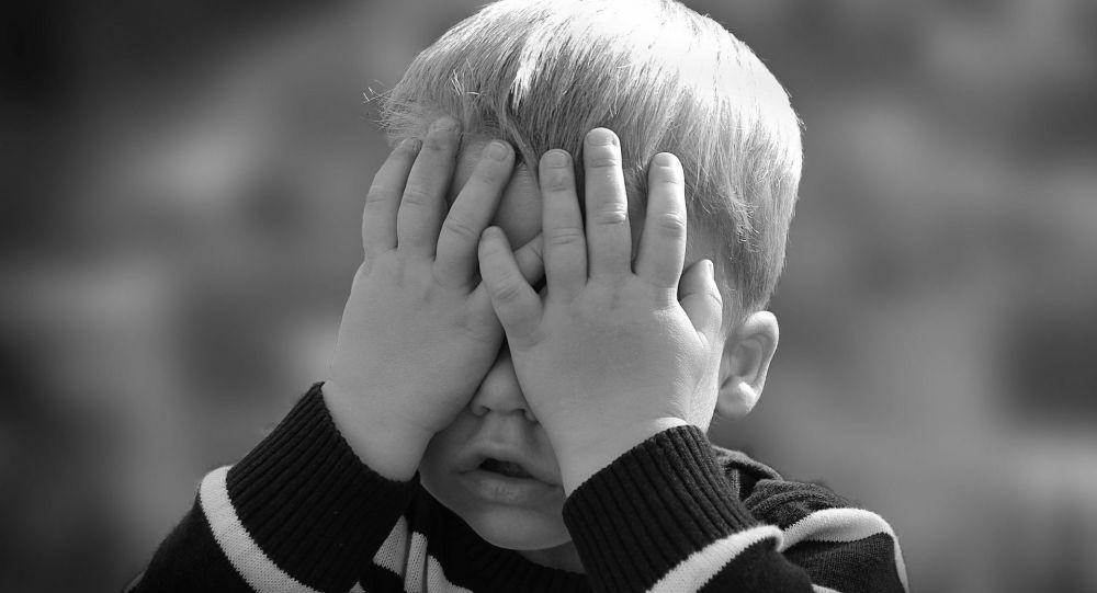 Un enfant cache les yeux