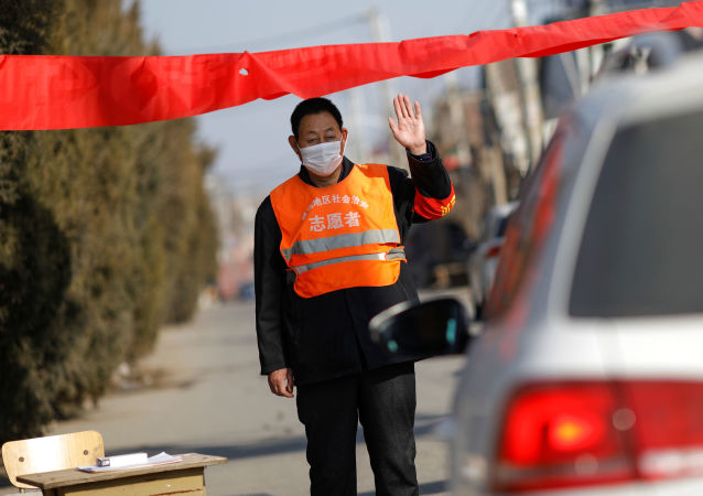 A village committee member wearing face mask and vest, stops a car for checking as he guards at the entrance of a community to prevent outsiders from entering