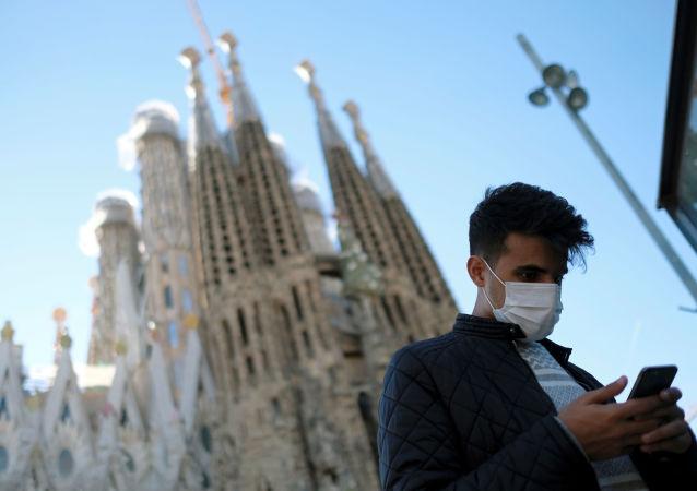 Un homme en masque de protection devant la basilique Sagrada Familia, sur fond d'épidémie de coronavirus, à Barcelone, en Espagne, le 2 février 2020.