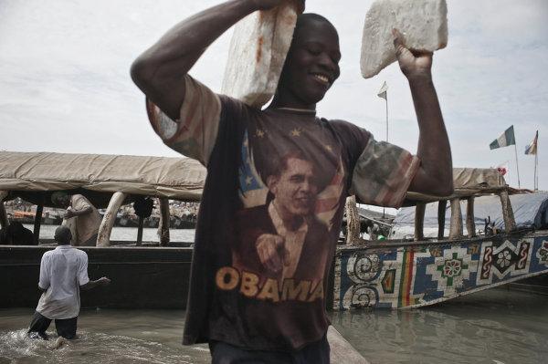 Рабочий несет плиты соли в порту города Мопти в Мали