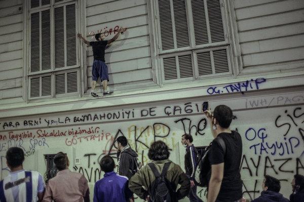 Один из протестующих на стене здания во время столкновения с сотрудниками полиции в Стамбуле