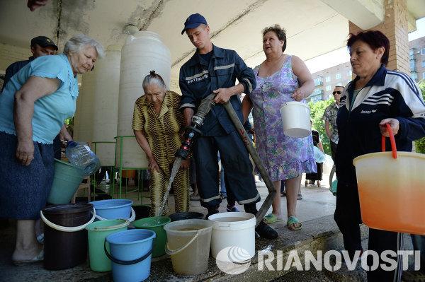 Жители Краматорска набирают воду, привезенную сотрудниками пожарной части